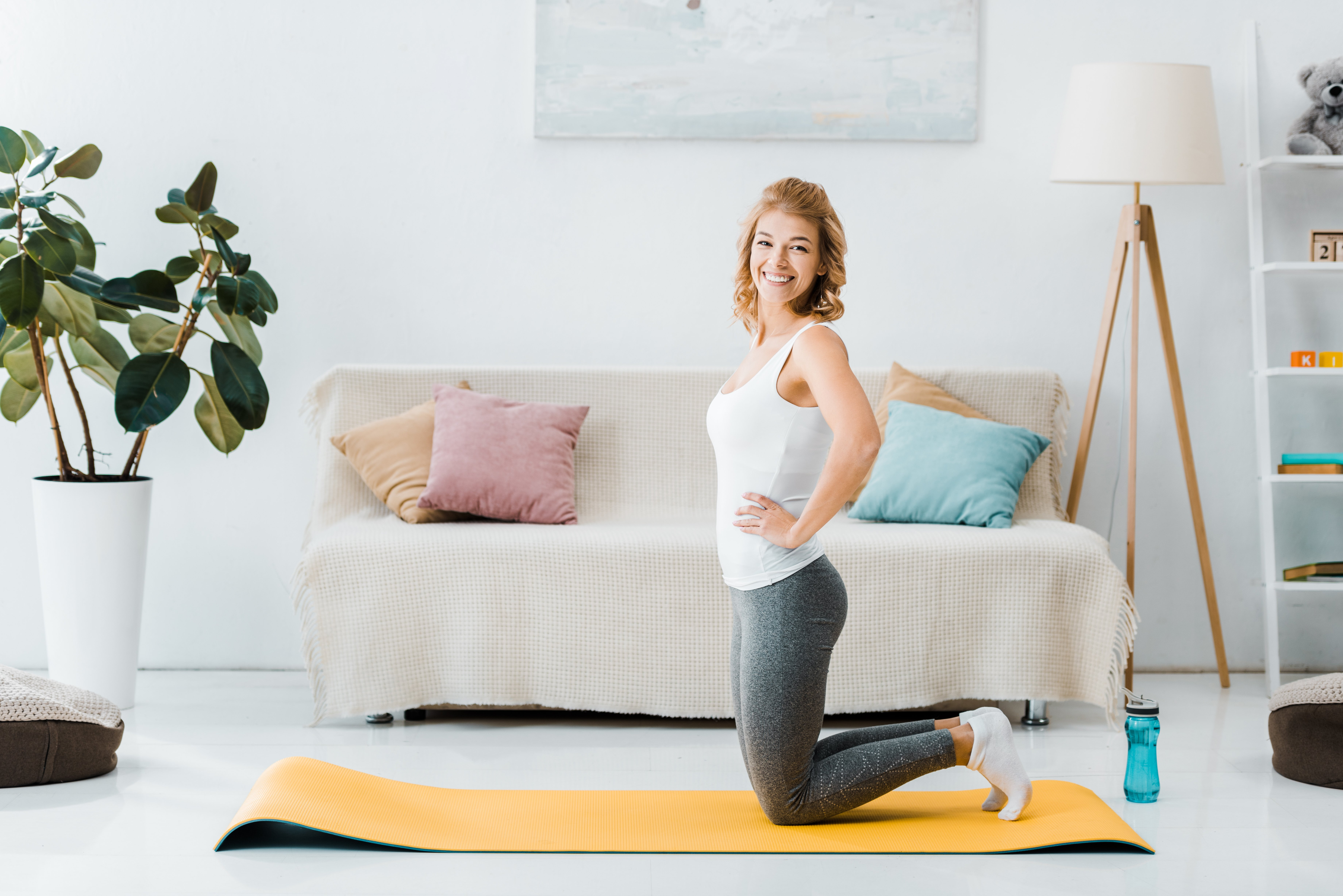 woman in sportswear kneeling on yellow fitness mat, looking at camera and smiling in living room